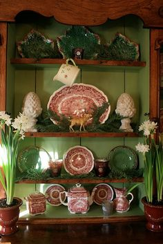 cedar and spruce branches tucked amongst the red transferware and green majolica plates.vignette design: Decking The Halls With Fresh Greens And Flowers