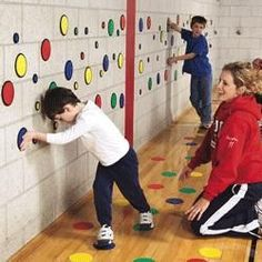 This activity assists children in learning about hand eye coordination and color coordination. The assistant tells them to put their feet on a color and they have to match it to the colors on the wall. This helps with using their mind to control where they put their hands and feet and focus on the colors.