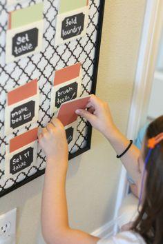Un tableau pour le suivi des corvées des enfants, avec des cartes de couleur dans des pochettes. Pourquoi pas !