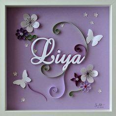 Tableau en quilling et papier découpé pour la naissance d'une petite fille nommée Liya. Décor à base de papillons et de fleurs dans une gamme de violets.