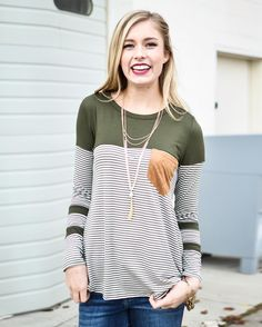 """Is this not the perfect stripe top? I have heart eyes for those details.   A little about this top: Olive Stripe Top With Suede Pocket Detail Price: $26 Size: S-L  To Purchase: Click the link in our bio click on the 3 lines at the top and go to """"Tops""""  Free Shipping Always  Hannah is 5'8 and wearing a small"""