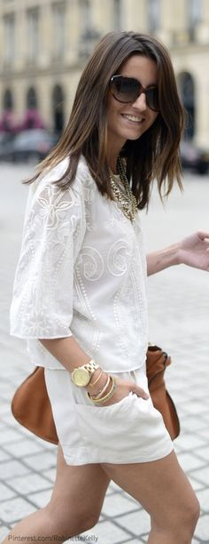 White embroidered blouse, white shorts, tan bag and statement necklace.