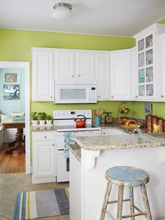 "The designer and homeowners made only one change to the already renovated kitchen: They replaced the stainless steel appliances with white ones to blend in with the cabinets. ""Together with the green walls and striped throw rug from Target, it's a bright, upbeat space,"" says Stephanie."