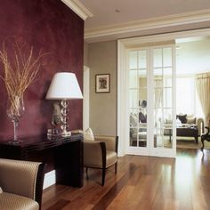 Polished wood floors complement the luxury home interior    (love the tan with crown molding, and maroon accent wall)