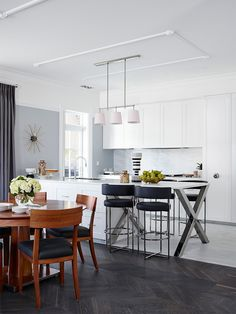 White, fresh kitchen with light grey walls and splash back faces elegant dining room