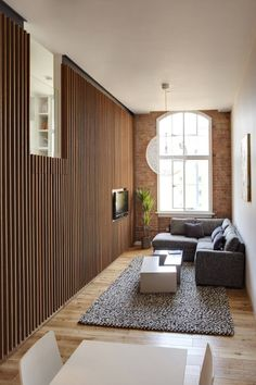 The thin room looks larger because the vertical lines on the walls make the ceiling seem taller and the furniture is placed in the most efficient way with having few pieces but the pieces are large, the hanging tv also saves room.