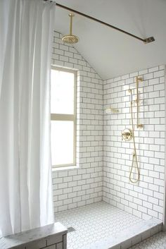 floor to ceiling subway tile with brass fixtures