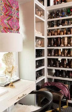Cara Loren - Amazing walk-in closet features a lucite desk with ivory cowhide drawers topped with a greek bust lamp placed under windows dressed in pink kilim roman shades.