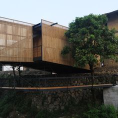 Bridge school in Fujian, China by architect Li Xiaodong.  The school is suspended over a creek and provides programatic space between two existing castles.