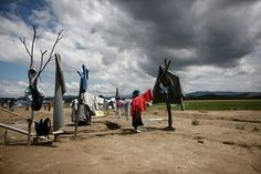 A refugee woman hangs out clothes to dry after heavy rainfall at the makeshift camp in Idomeni near the border between Greece and Macedonia