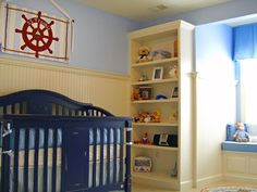 Nautical boys nursery...love the 'S.S Frankie' nautical wheel and that navy crib. Simple beadboard and paint completes the look.