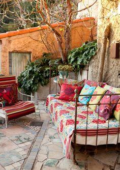Terrasse im Bohemian Stil. Das Metallbett mit bunten Kissen ist ein echter Hingucker.