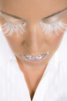 Exaggerated white feather eye lashes with bejeweled lips.