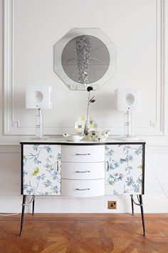 A 50s cabinet with a flower motif printed onto the laminate. The Perspex lamps are from Mead's travels in the US. The Mosaic china is by Jessie Tait for Midwinter.