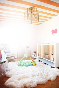 Love the oversized sheepskin rug and the yellow stripey ceiling. #nursery #decor