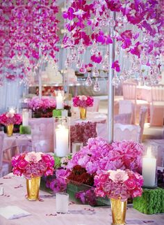 insanely beautiful wedding centerpieces - tall centerpiece of purple orchids hanging over a silver pole forming a canopy, resting on a bed of pink peonies