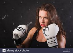 Download this stock image: Girl in boxing gloves on a black background. - HYDH3T from Alamy's library of millions of high resolution stock photos, illustrations and vectors.