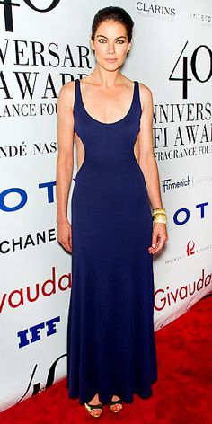 MICHELLE MONAGHAN  Someone's been doing her side bends and sit-ups! The actress tries the hot-right-now cutout dress trend with a minimalist vintage Halston frock, and adds metallic peep-toes and a matching bangle at the FiFi Awards.