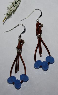 Cluster of three faceted tiara crystals in opaque sky blue have been threaded with leather cord that has been twisted, knotted, glued and