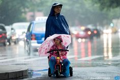 """CHINA, Shanghai : A woman pushes a child on a tricycle through heavy  rain in Shanghai on June 15, 2015. With today's rain the local media  announced the beginning of the """"plum rain"""" or East Asian rainy  season,starting over the middle and lower reaches of the Yangtze River.   AFP PHOTO / JOHANNES EISELE"""