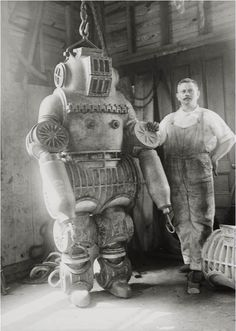 Chester E. Macduffee next to his newly patented, 250 kilo diving suit, 1911. A rather curious design for a diving suit. It seems apparent that Chester did not take into account the weight of his invention. This suit would drop to the bottom of the ocean like a lead zeppelin leaving its occupant completely trapped. Even Houdini wouldnt be able to escape this device.