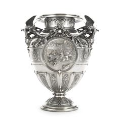 A Victorian silver large vase-form race trophy,the base chased with Celtic knots, the stem applied with studs, lower body chased with alternating stylized flowers and thistles, each side with a roundel, one boldly embossed with a medieval horse racing scene, below applied acorn branches centered by a bell, the sides with stylized sunflowers, the handles topped by belled falcons, Hunt & Roskell Ltd., London, 1878. -- Sotheby's