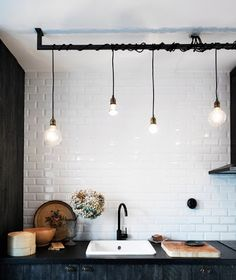 Industrial bare bulb lighting, metro tiles, black kitchen units. Love this monochrome kitchen.