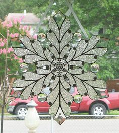 This original design snowflake was made with hand-cut clear textured glass, faceted glass jewels, glass nuggets, beveled glass, and a metal snowflake