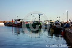 Photo about A small fishing port in Ampolla Spain along the mediterranean coast with its small boats is quiet as the sunsets. Image of spain, tugs, sunsets - 81012334 Sunset Images, Small Boats, Sunsets, Spain, Fishing, Coast, Ships, Stock Photos, Travel