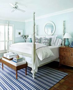 Beautiful bedroom with pale blue walls. Pretty white fluffy bedding!