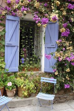 A romantic outdoor space featuring delicate purple chairs, country window shutters & vibrant flowers. I might just put the wrought iron and shutters leading out to the woods