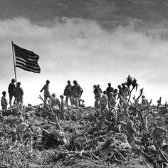 Alot of United States Marines gather around to see the raising of the American flag atop Mount Suribachi, after the fierce battle of Iwo Jima.