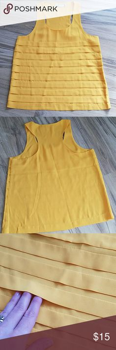NWOT Just Fab yellow layered tank This tank is new, never worn. Super cute deep yellow layered tank with a slight high low cut. This top is perfect to dress up with some skinny jeans and heels or dress down with some flats and a cardigan!  Last picture show true color of top. The back does not have layers on it like the front.  Size Medium  Length 23 from shoulder to hem Back length 23.5 Chest 18 inches across Waist 20 inches across  Bundle and save! JustFab Tops Tank Tops