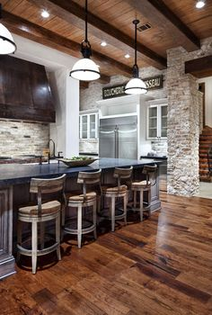 Luxury Home in Texas: When Rustic Meets Modern.. Love the barn floors and island...and vent hood! Love the mixture of wood, stone, and metal. The bar stools remind me of a saloon! love love love