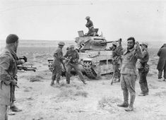 New Zealander soldiers recapture a Matilda tank previously captured by the Germans and take prisoner its German crew. It had been knocked out by an anti-tank gun after an attempt to break through the Allied lines 3 December 1941.