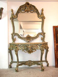 French style carved & gilded crackle console finished in a model of precision in carvings, with two gilding levels, painted in green trianon color and full of garlands, scrolls, sea-shells, cornucopias, pendants, heavy doubled x stretcher & dentil carved frieze plus a marble top.  REF: AZL8210  H: 203 cm   W: 140 cm  D: 50 cm   http://www.azharyantiques.com/consoles/AZL8210.html