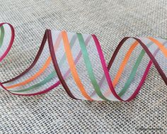 Inventive colorful stripes woven onto a sheer mesh, finished with a wired edge. The screen like texture of the mesh contrasts with the grosgrain stripes in cranberry red, forest green, pumpkin orange and bark brown. From the Cottage Crafts Online shop on Etsy.