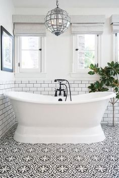 White and black bathroom features top half of walls painted white and bottom half of walls clad in white subway tiles finished with black grout lined with a glass faceted lantern hanging over a roll top bathtub fitted with an oil rubbed bronze tub filler placed atop a white and black Cement Tile Shop Bordeaux Tiles. #Bathtubs