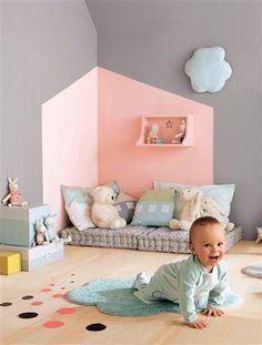 De vorm van een huis geschilderd op de muur in een hoek van de kamer en aangekleed met (oude) kussens en knuffels.