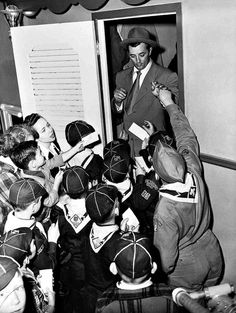 Robert Mitchum stands in the doorway to his dressing room while being mobbed by boy scouts on the set of The Racket, 1951.