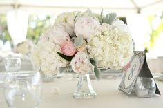 Some of the centerpieces will be low silver compotes filled with white hydrangeas, blush peonies, white stock flowers, blush spray roses and hints of gray dusty miller and seasonal greenery surrounded by votives.