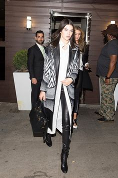 Kendall Jenner wears a printed coat, long white blouse, leather leggings, lace-up boots, and a black satchel