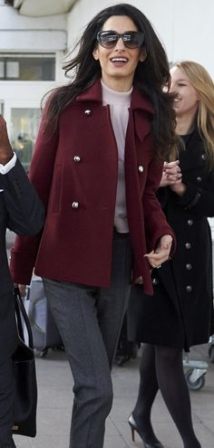 Amal Clooney in a blush turtleneck and short deep red coat.