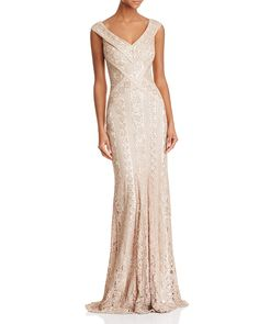 A dramatic V front and back echo the sleek angled lines of Tadashi Shoji's magnificent sequined lace gown, designed to channel your inner goddess with its waist-slimming silhouette and floor-grazing h
