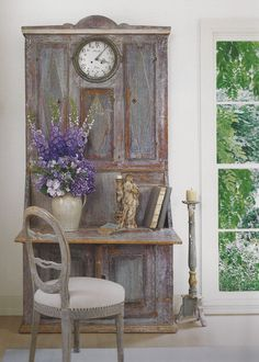 Purple delphinium, hydrangeas and iris are a beautiful complement to weathered gray antique secretary.  From Houses of Veranda.
