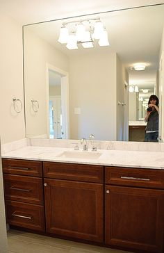 "sheet mirrors – the key to making them look expensive as opposed to ""builder"" is to make sure that they stretch from the backsplash to the ceiling, and from wall to wall.  Such large mirrors also bounce around a ton of light."