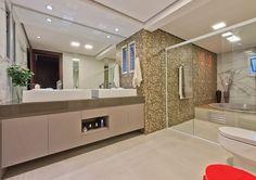 No banheiro da suíte, uma combinação de vários porcelanatos mostra a versatilidade do décor. Na área da banheira, foram colocadas duas lâmpadas RGB, que mudam de cor, incrementando os banhos e proporcionando uma sensação de bem-estar e relaxamento.