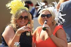 Cheers! A pair of ladies, both in spectacular fascinators, enjoy a bottle ofMoët & Chando...