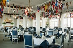 """Club burgees flutter overhead in the main dining room. """"Now that the club has been raised, the dining room has even better views of the bay,"""" notes Lucas. The custom Harbinger dining chairs are upholstered in sleek navy leather from Architex."""