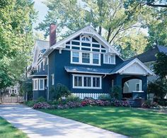 Deep, inky blue on the stucco siding gives the impression of a solidly constructed home with real permanence in the landscape. Bright white trim provides a clear contrast with the dark body color and keeps architectural details, such as the patterned stick-work in the roof and porch gables, from being upstaged.     Shown: Bunglehouse Blue (body); Pure White (trim); from Sherwin Williams.